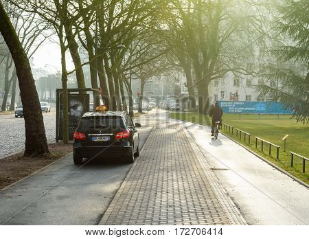 STRASBOURG FRANCE- FEB 2 2017: Mercedes-Benz taxi van exiting special taxi parking near the European PArliament bus station - cyclist biking on special lane