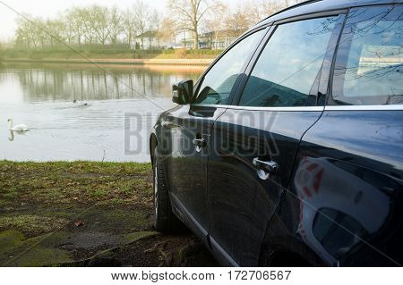 Detail of blue car parked in front of a lake with elegant swans on the blue surface
