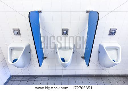 Urinals for boys on white wall with blue partitions in high school