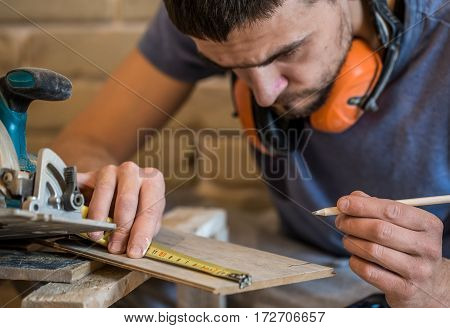 The Man Makes The Measurements On The Board
