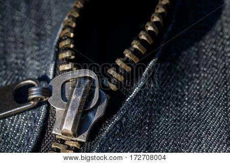 Close up and detailed shot of a metallic zip on denim