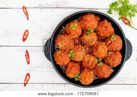Meat balls in spicy tomato sauce served on a cast iron pan on a white wooden background. The top view.