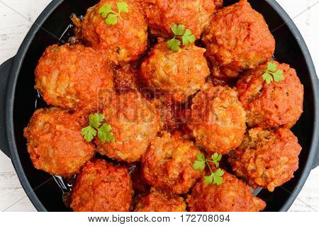 Meat balls in spicy tomato sauce served on a cast iron pan on a white wooden background. The top view. Close up