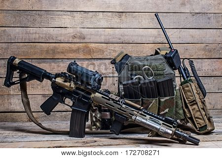 Assault rifle with telescopic sight,bulletproof vesta,mmo and radio on wooden background