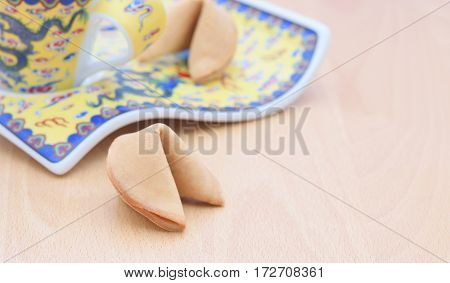 A fortune cookie on the table with porcelain plate
