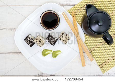 Traditional eastern dish with salmon shrimp - sushi rolls on a white plate. The top view