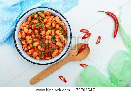 White large beans in sweet and sour tomato sauce in a bowl on a light background. The top view. Vegetarian cuisine. Lenten meal.