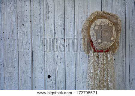 Old lady's hat from point with pearls hangs on the right on old white wooden wall