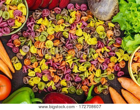 Colorful pasta on a table with fresh vegetables (beets greens carrots tomatoes peppers). Healthy food concept. The top view