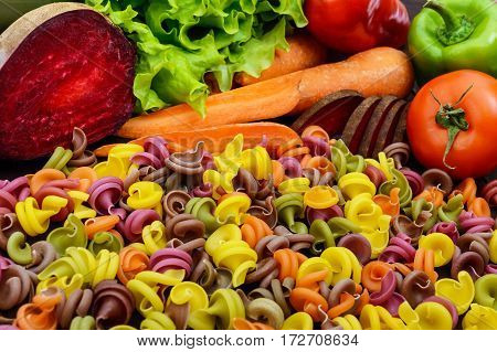 Colorful pasta on a table with fresh vegetables (beets greens carrots tomatoes peppers). Healthy food concept. Close up