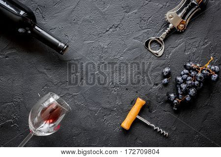 glass bottle of red wine with wineglass on dark texture background top view mock-up