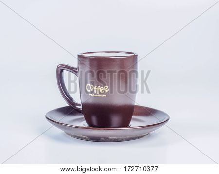 Close up dark brown coffee cup standing on a saucer isolated on white background. Side view.