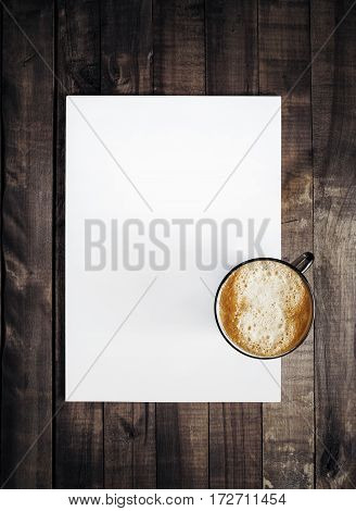 Blank letterhead and coffee cup. Template for branding identity on vintage wooden table background. Mockup for placing your design. Top view.