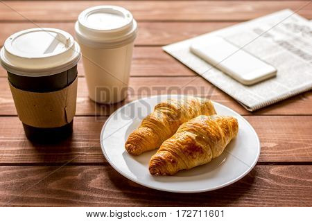 Businessman morning coffee in paper cup with croissant and newspaper on wooden table