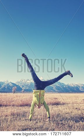 Color toned picture of a young woman upside down on a meadow having fun outdoors concept Grand Teton National Park Wyoming USA.