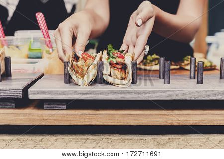 Selling mexican fast food. Female street vendor hands make taco outdoors. Snacks of commercial kitchen.