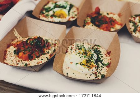Street vendor's hummus with eggs and beef sold outdoors. Eastern cuisine snacks closeup, in craft package. Fast food for commercial kitchen.