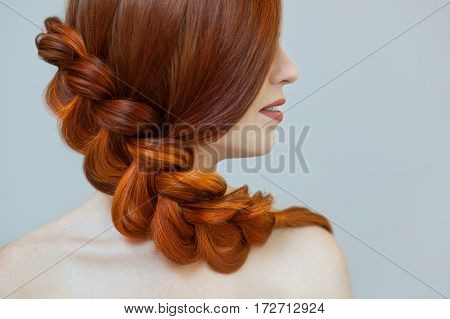 Beautiful girl with long red hair braided with a French braid in a beauty salon. Professional hair care and creating hairstyles. poster
