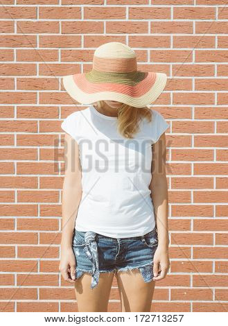 Portrait of romantic girl in straw hat against brick wall, elegant lady in hat on summer vacation