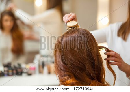 Hairdresser Combing Her Long, Red Hair Of His Client In The Beauty Salon. Professional Hair Care And
