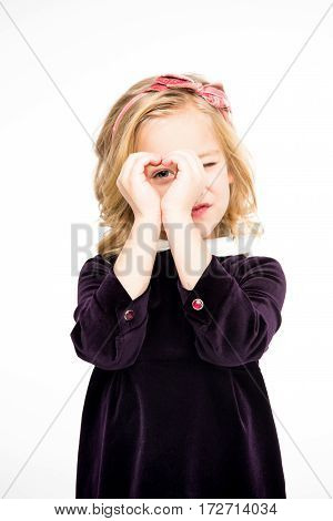 Beautiful little girl gesturing heart hand sign on white