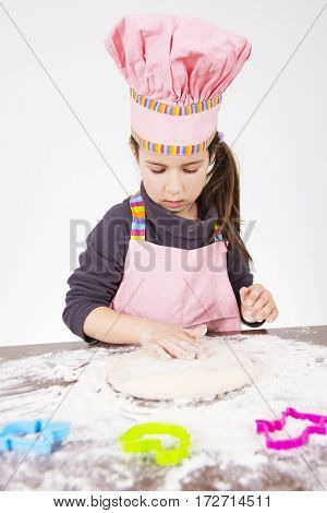 Cute girl preparing pastry for bread or pizza