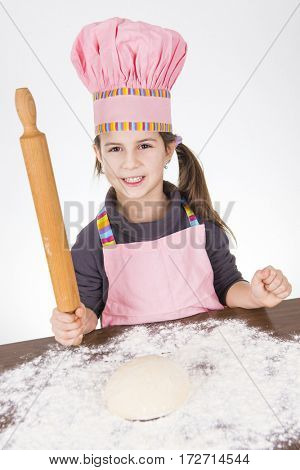 Young girl in kitchen preparing pastry for bread