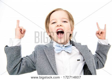 Portrait of excited little boy showing rock sigh with fingers