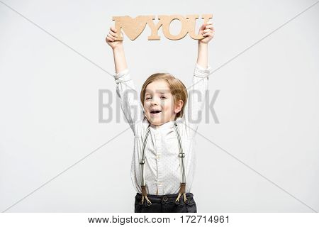 Excited little boy holding wooden words