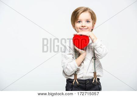 Little boy holding red heart sign smiling and looking at camera