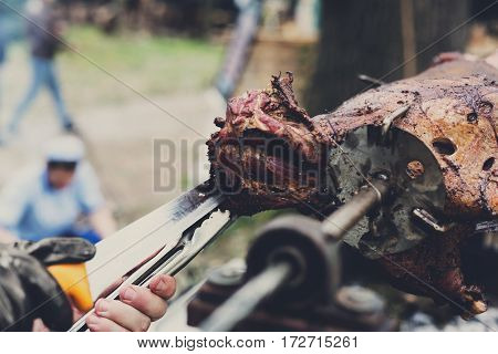 Barbecue picnic at country fair. Lamb roasted at spit closeup. Grill, big piece of meat at rolling skewer. Street vendor, professional chef hands cooking bbq food. Catering concept, vertical