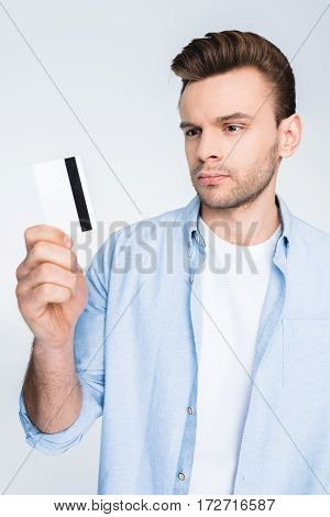 Handsome Young Man Holding Credit Card In Hand On White