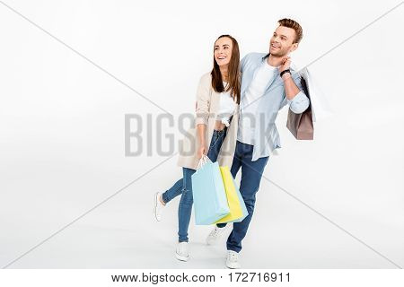 Happy young couple with shopping bags embracing and looking away on white
