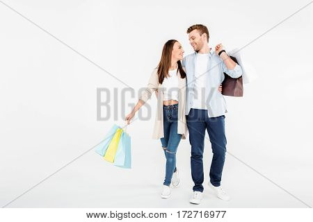 Happy young couple with shopping bags hugging and looking at each other