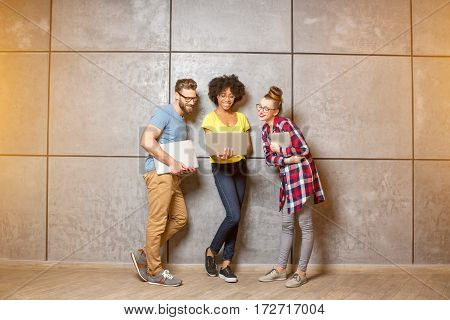 Multi ethnic coworkers dressed casually in colorful clothes working together with laptops on the gray wall background