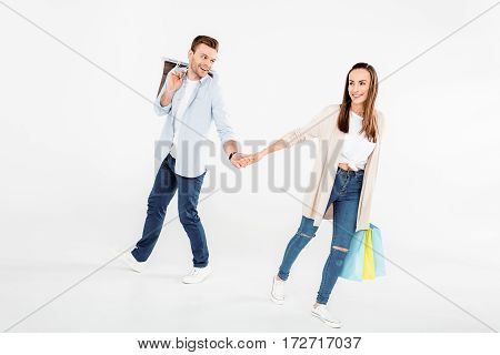Happy young couple with shopping bags holding hands on white