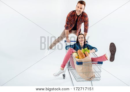 Young Smiling Man Pushing Shopping Cart With Happy Woman And Grocery Bag On White