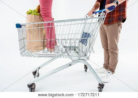 Low section of man pushing shopping cart with young standing woman and grocery bag