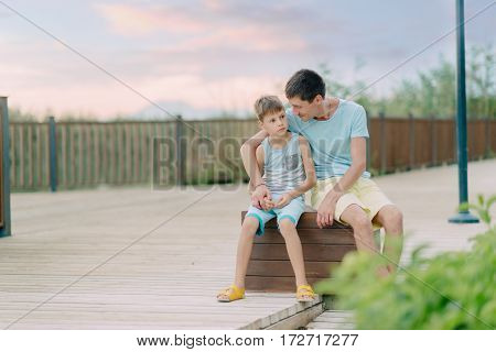 summer day, father and son in a park sitting on a wooden bench