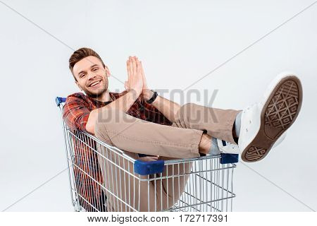 Handsome young man lying in shopping trolley and smiling at camera