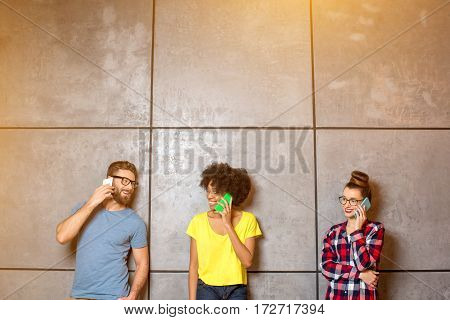 Multi ethnic coworkers dressed casually in colorful clothes talking with smart phones on the gray wall background. Wide shot with copy space