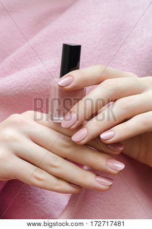 Beautiful female hand with warm pink nail design holding nail lacquer bottle.