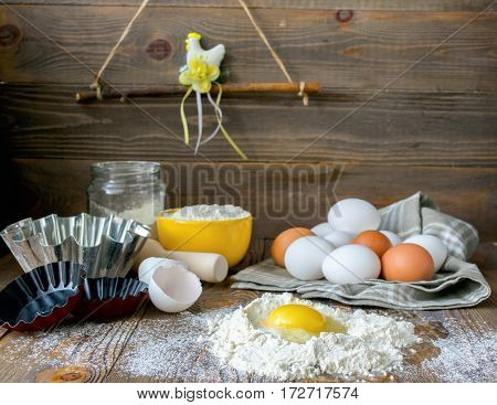 Fresh chicken egg broken kitchen wooden table for making a festive Easter cake dark background. Front viewhorizontal frame.Place for text