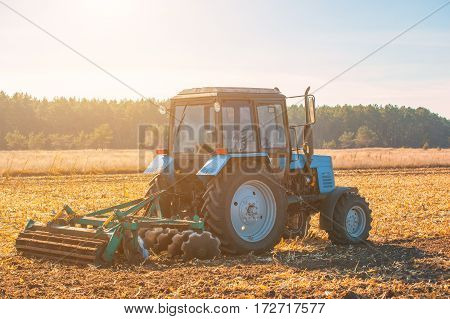 large blue tractor plow plowed land after harvesting the maize crop on a sunny clear autumn day. Part of the cultivator steel round discs in a row close-up. Work agricultural machines. Harvest.