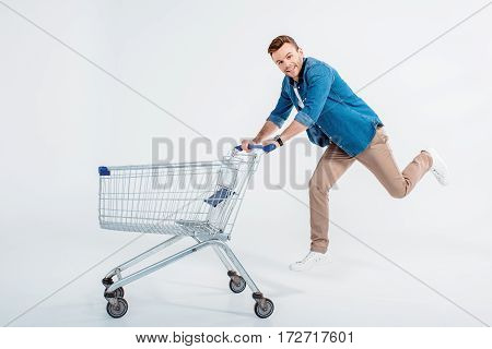 Happy young man running with shopping trolley and smiling at camera