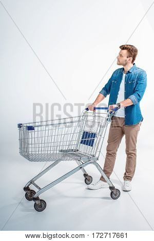 Full length view of handsome young man standing with shopping trolley and looking away