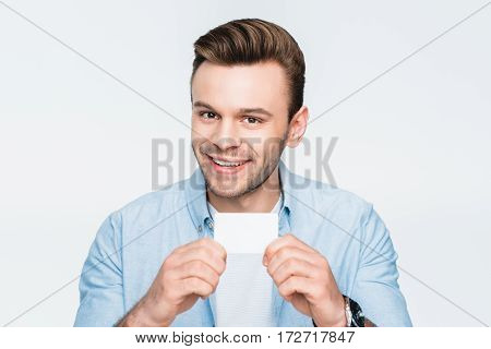 portrait of smiling man showing credit card and looking to camera on white