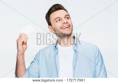 portrait of smiling man holding credit card in hand and looking away on white