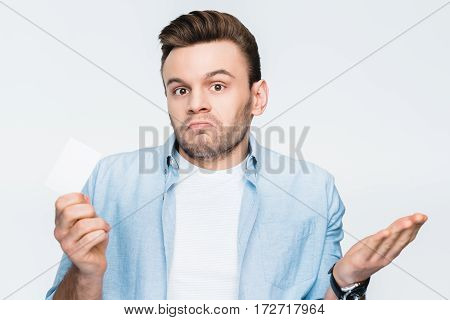 portrait of upset man holding credit card in hand and looking to camera