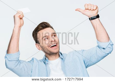 portrait of happy man holding credit card and looking away on white